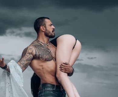 A sexy man holding a beautiful woman over his shoulder