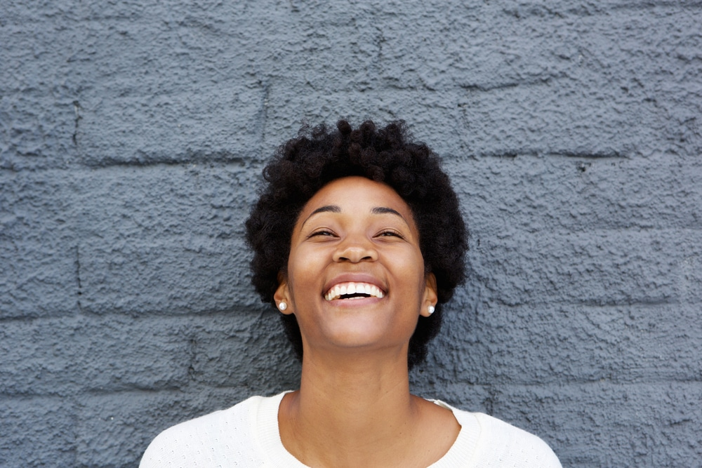 Beautiful woman smiling against gray, brick wall