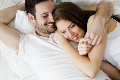 clothed young couple laying in bed. The man has his arm around the woman. Her head is resting on his chest and they are smiling.