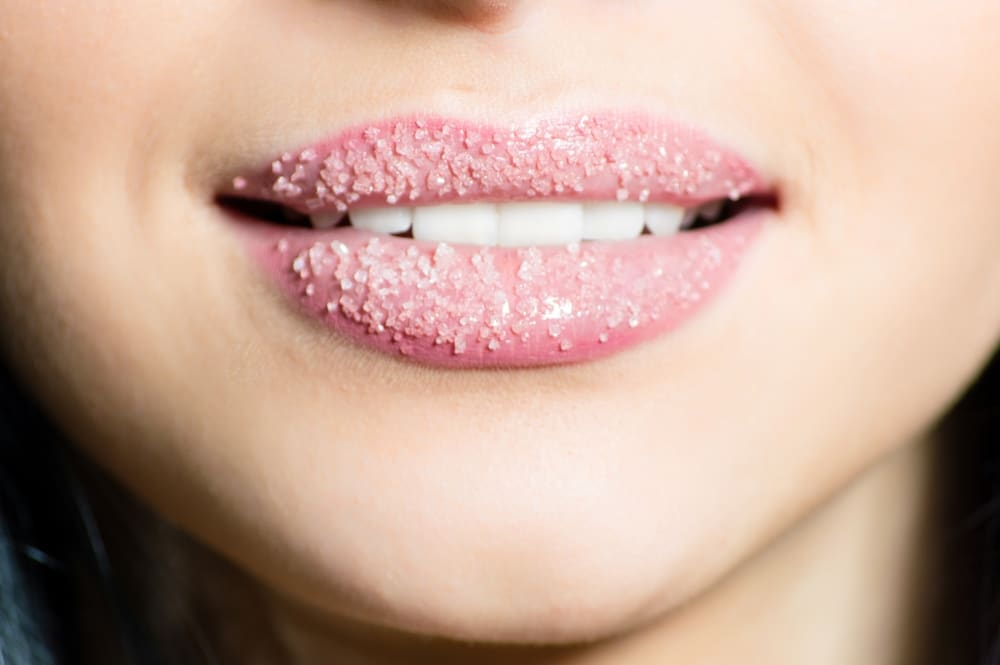 Close up of a woman's pink lips covered in a sugar scrub