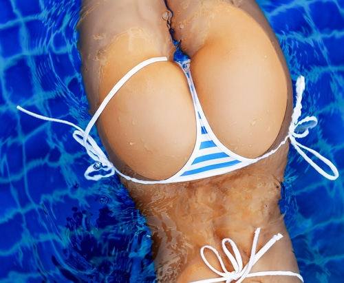 Closeup of a woman's butt. She is in the pool wearing a string bikini bottom. her butt is full and smooth