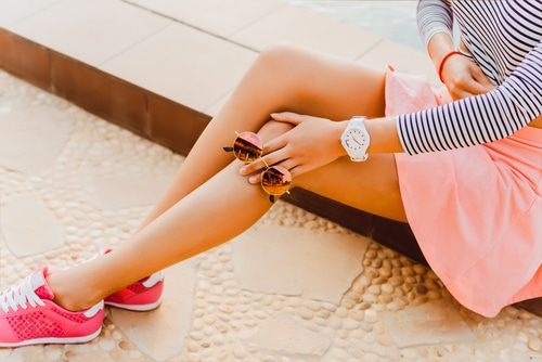 Photo of a woman's legs. The individual is sitting on the sidewalk with legs extended. Her legs are attractive and smooth