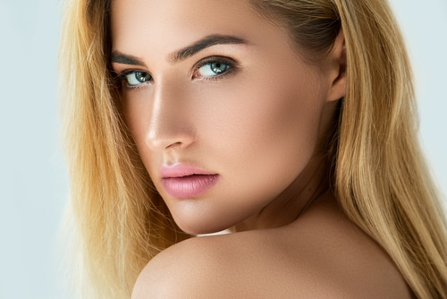 Close up of an attractive blonde woman with full, dark eyebrows