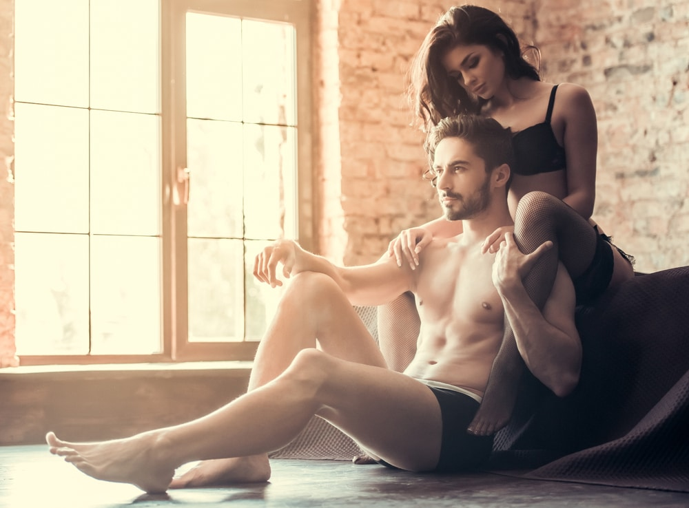 attractivecouple in their underwear. man is sitting on the floor and the woman is hugging him from behind