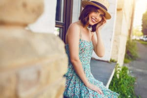 Pretty girl in sun dress, wearing straw hat, smiling at camera on a historic street