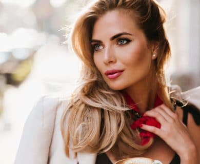Attractive blonde, in jacket outside, sunlight highlighting her beautiful features