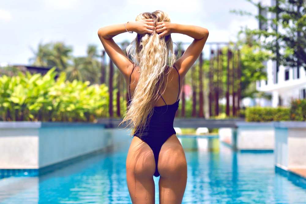 Photo of a woman at luxurious pool, her back is facing camera, wearing sexy one piece, her butt looks firm and toned