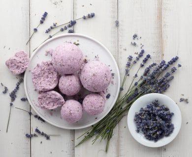 Handmade lavender bath bombs and lavender flowers on white wooden planks