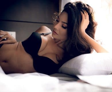 sexy woman lying in bed, black bra, lifted breasts