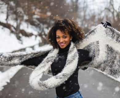 pretty woman, curly hair outside on a snowy day, dancing and twirling in the snow