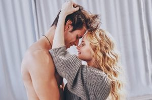 attractive couple, about to kiss, nose to nose, woman is running her hands through the man's hair