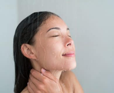 Asian woman taking a hot shower, she looks relaxed, only her face and shoulders are visible