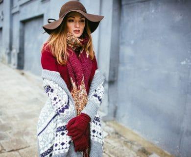 woman in beautiful winter fashion walking along a cobblestone street.