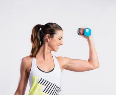 happy woman doing a bicep curl with a free weight