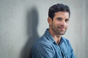 Handsome man in denim shirt leaning against gray wall smiling at camera
