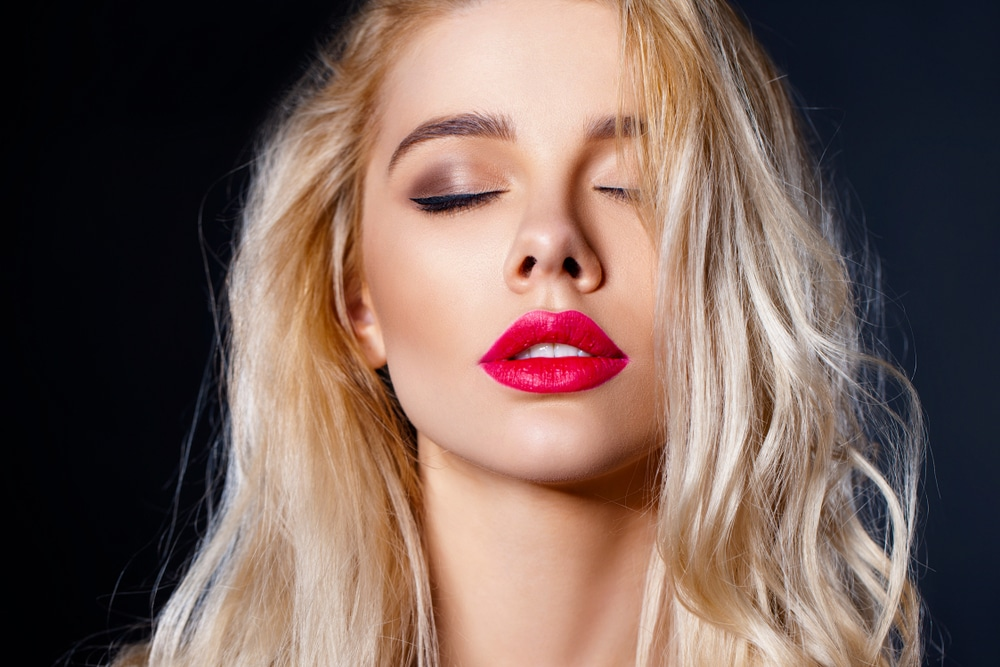 Photo is of the face of a beautiful young woman. Her plump lips are the center of the photo, and she is wearing dark pink lipstick. She has long, blonde, wavy hair. Her head is tilted slightly backward, her eyes are closed, and her mouth is slightly open. The background is black, with the light being focused on the young woman's face.