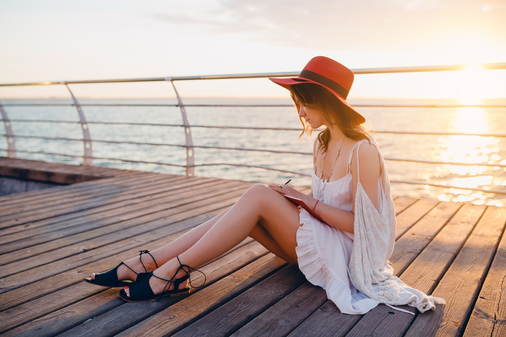 Photo is of a beautiful woman sitting on a pier. She has long, straight brown hair. She is wearing a white dress and a red sun hat, and appears to be writing in a journal. Her legs are showing and appear to be smooth and without any cellulite. The background is of a sunset.